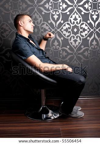 Cool guy sitting on an armchair - stock photo
