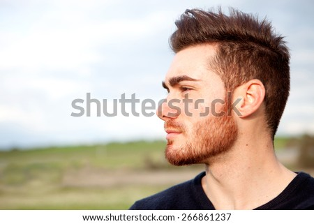 Cool handsome guy with beard looking at side - stock photo