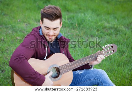 Cool handsome guy with beard playing guitar at outside - stock photo