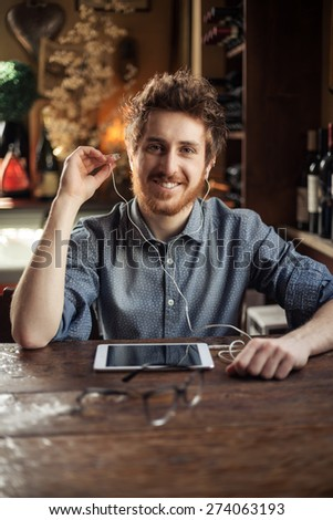 Cool hipster sitting at bar table and listening to music with his tablet using earphones - stock photo
