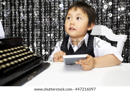 cool little boy adds up numbers on a calculator - stock photo