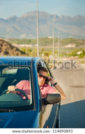 Cool looking guy using is phone while driving - stock photo