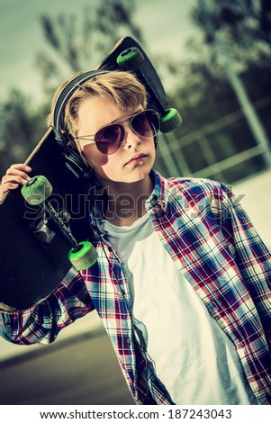 cool looking skater boy, with sunglasses and headphone vintage effect added - stock photo