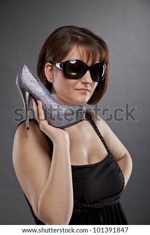 cool looking young woman with sunglasses holding a shoe - stock photo