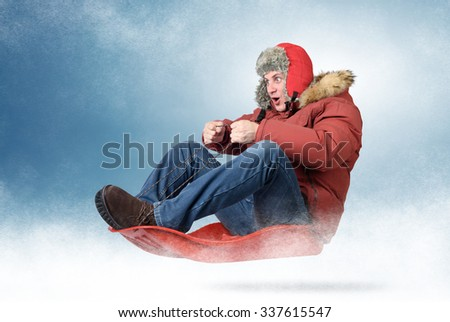 Cool man fly on a sled in the snow, concept winter driving - stock photo