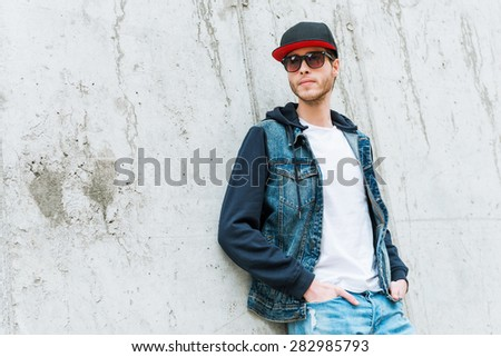 Cool man in cap. Confident young man in headwear holding hands in pockets while leaning at the concrete wall  - stock photo
