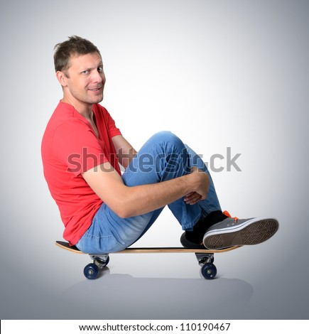 Cool man sitting on a skateboard deck - stock photo