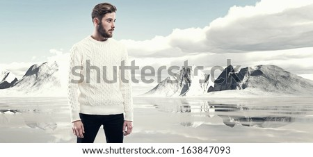 Cool man with beard in winter fashion. Wearing white woolen sweater. Outdoor in snow mountain landscape. - stock photo