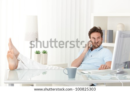 Cool man with feet up on desk making mobile phone call, typing on keyboard, smiling, looking at computer screen. - stock photo