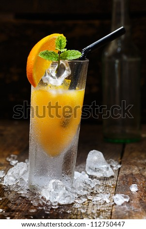 Cool Orange Alcohol Drink with crushed Ice on wooden table for drink concepts - stock photo
