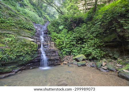 Cool refreshing waterfall hidden in a mysterious forest of lush greenery - stock photo
