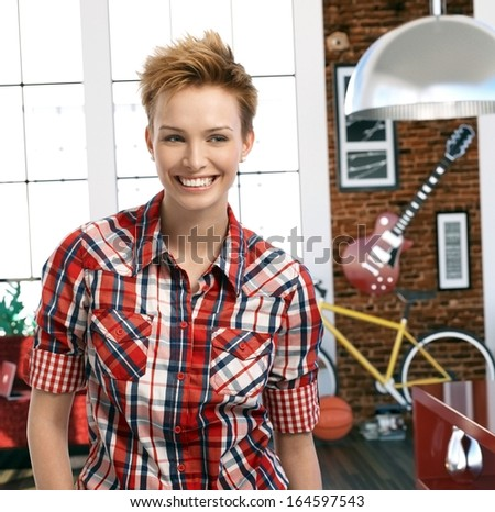 Cool short haired girl at home looking away laughing. - stock photo