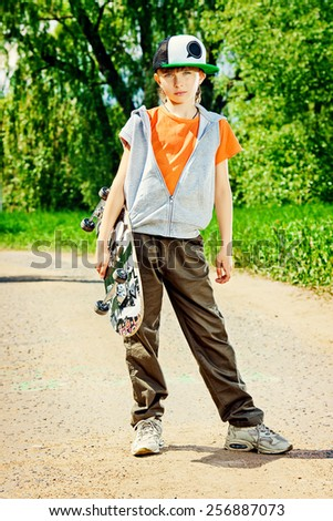 Cool teen boy with his skateboard on the street. Childhood. Summertime. - stock photo