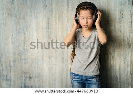 Cool teen girl enjoys the music in headphones. Studio shot. - stock photo