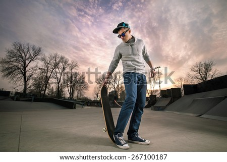 Cool teenage boy with skateboard in the skate park - stock photo