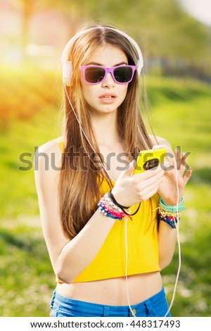 Cool teenage girl with headphones and smart phone outdoors in park. Beautiful young woman with sunglasses, wearing vibrant colored clothes, listening to music in summer. Vibrant colors, mild retouch. - stock photo