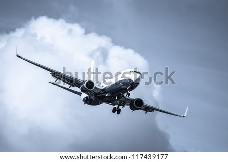 cool toned passenger jet on landing approach through a cloudy sky - stock photo