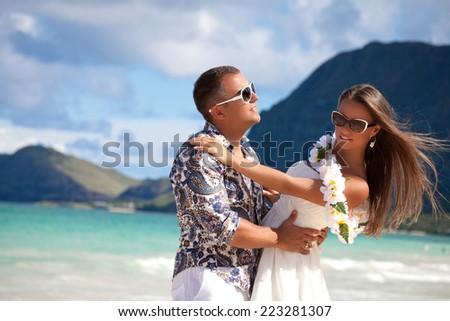 Cool trendy modern couple on summer holidays vacation on tropical Hawaiian beach. - stock photo