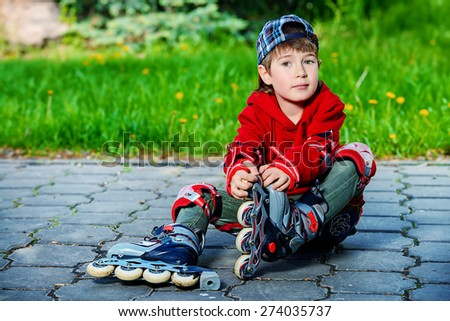Cool 7 year old boy rollerblades on the street. Childhood. Summertime. - stock photo