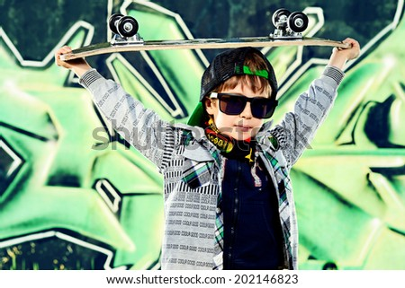 Cool 7 year old boy with his skateboard on the street. Graffiti background. Childhood. Summertime. - stock photo