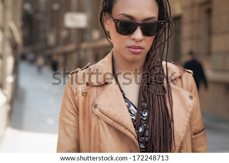 Cool young African woman wearing sunglasses on the street. - stock photo