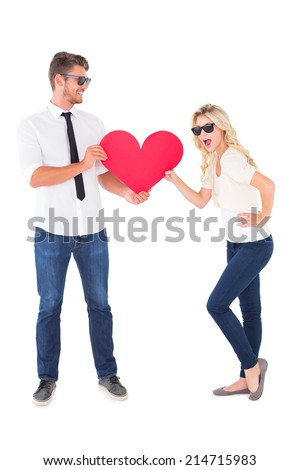 Cool young couple holding red heart on white background - stock photo