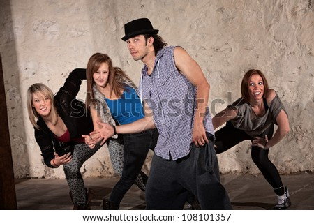 Cool young Hispanic dancer with group in underground setting - stock photo