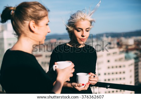 Cool young women talking in roof top coffee shop - stock photo