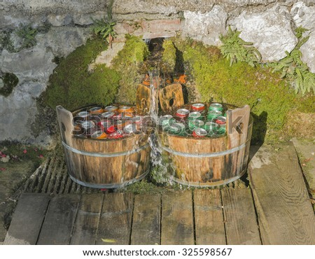 Cooling metal aluminum beverage drink cans in wooden tubs with running water outdoor - stock photo