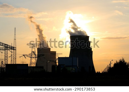 Cooling towers against the sun and Electricity towers - stock photo
