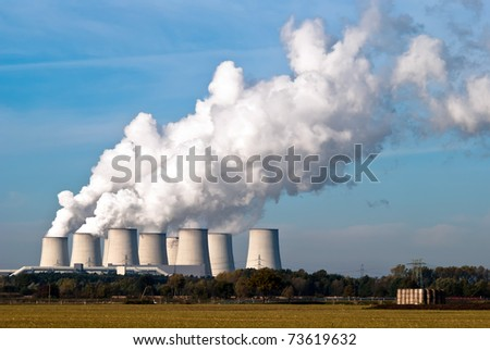 Cooling towers of a power plant with steam clouds and sky - stock photo