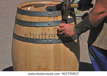 Cooper hands fixing wine wood with chisel and hammer. Making a wooden barrel. Cooperage - stock photo