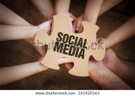 Cooperation - Jigsaw Puzzles in Teams Hands with social media on it - stock photo