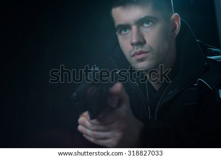 Cop holding pistol and aiming at criminal - stock photo