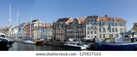 COPENHAGEN, DENMARK - AUGUST 15: Boats at the harbor in Nyhavn on August 15, 2012 in Copenhagen. Nyhavn is a 17th century embankment, canal and entertainment area in Copenhagen. - stock photo