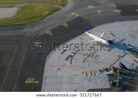 COPENHAGEN, DENMARK - AUGUST 01, 2015:  SAS airlines plane parked in Copenhagen. Airport is one of the oldest international airports in Europe. Aerial view. - stock photo