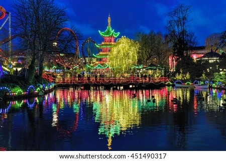 COPENHAGEN, DENMARK - DECEMBER 14, 2015: Evening view of the Tivoli Gardens with Chinese pagoda on the shore of the pond. The Tivoli Gardens is the most-visited theme park in Scandinavia. - stock photo