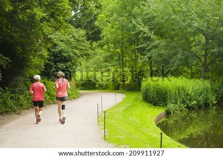 COPENHAGEN, DENMARK - JULY 3: Women running in the park Frederiksberg Have on July 3, 2014 in Copenhagen. - stock photo
