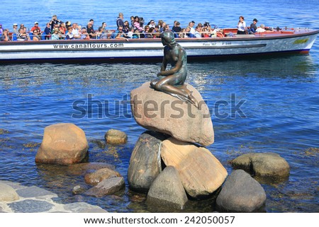 Copenhagen, Denmark - June 30, 2014: Touristic vessel pass near the iconic statue of The Little Mermaid, Copenhagen, Denmark - stock photo