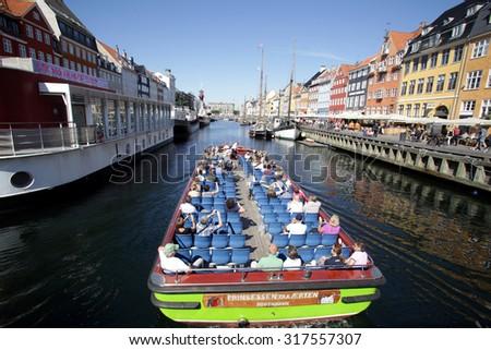COPENHAGEN, DENMARK - SATURDAY, AUGUST 22, 2015: A tourist boat in Copenhagen.  Nyhavn is a 17th-century waterfront, canal and entertainment district in Copenhagen  - stock photo