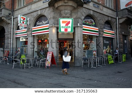 COPENHAGEN, DENMARK - SATURDAY, AUGUST 22, 2015: Pedestrians walk past a 7-Eleven convenience store in Copenhagen.  - stock photo
