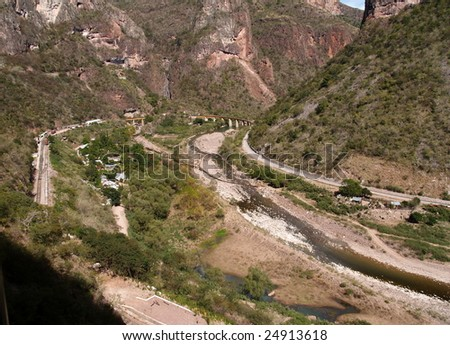 Copper Canyon railway winds its way into the interior of Mexico over a curving bridge  seen here from the third of three levels of train track - stock photo
