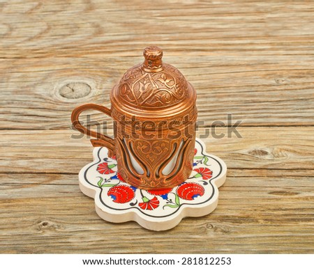Copper cup of Turkish coffee on a ceramic base with an ornament on a wooden background - stock photo