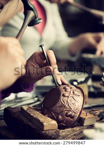 Copper master, hands detail of craftsman at work. - stock photo