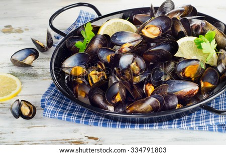 Copper pot of gourmet mussels served on a napkin garnished with lemon and parsley. - stock photo