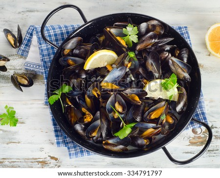 Copper pot of gourmet mussels served on a napkin garnished with lemon. Top view - stock photo
