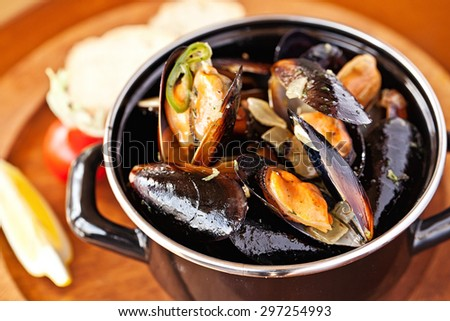 Copper pot of gourmet mussels served on a wood plate garnished with fresh herbs and lemon for a tasty seafood meal - stock photo