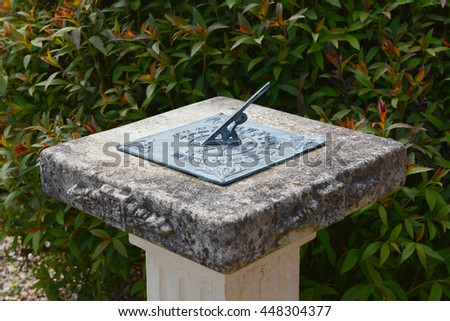 Copper sundial on a stone pedestal against a leafy Japanese spiraea shrub in a garden - stock photo
