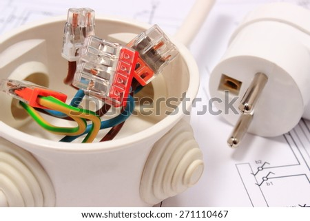 Copper wire connections in electrical box and electric plug lying on construction drawing of house, accessories for engineering work, energy concept - stock photo