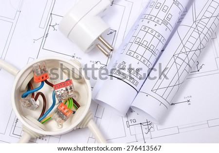 Copper wire connections in electrical box, electric plug and rolls of electrical diagrams on construction drawing of house, energy concept - stock photo